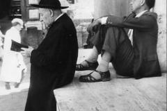25 Publifoto Napoli 1951. Un operaioi disoccupato si riposa dal lungo girovagare sulle scale di un cinema di periferia,ed il buon prete di provincia,ignaro,legge il breviario.
